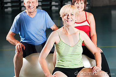 People in gym on exercise ball