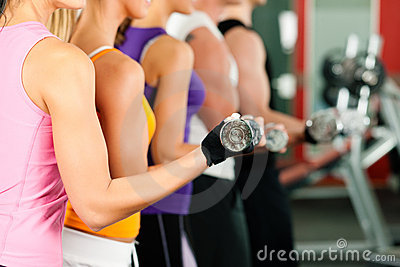 People in gym exercising with dumbbells