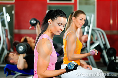 People in gym exercising with weights