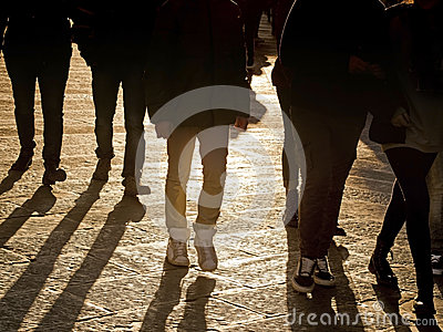 People legs walking in the city at sundown