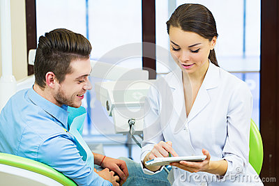 People, medicine, stomatology and health care concept - female dentist showing teeth x-ray scan on tablet pc computer screen to ma Stock Photo