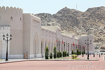 People near wall of Sultan s Palace in Oman.