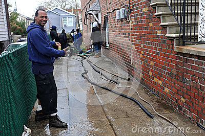 people pumping water out of building basement editorial photo image