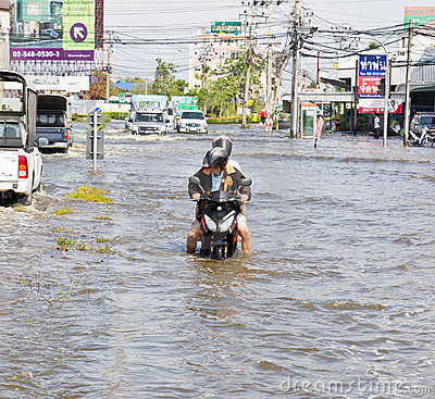 People push motorcycle on water flood road Editorial Image