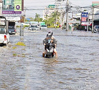 People push motorcycle on water flood road Editorial Image