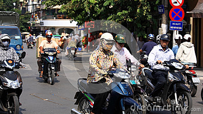 People ride motorbikes on busy road in Hanoi