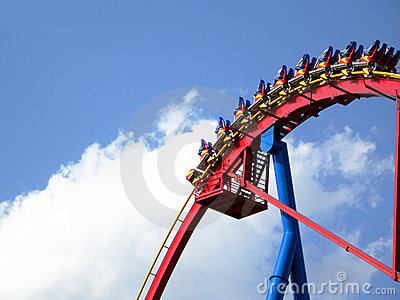 People in roller coaster againt bright blue sky