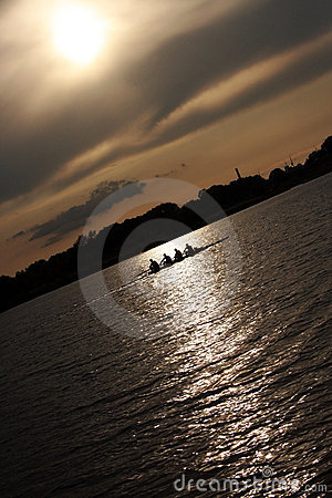 People rowing boat at sunset