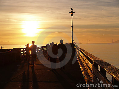 People silhouette on pier at sunset