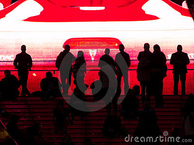 People silhouetted against huge video screen.