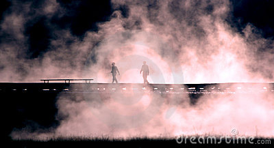 People Silhouetted Against Mist