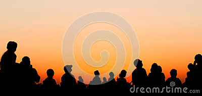 People silhouettes watching sunset sky