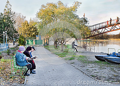 People sit on a park bench and reading newspapers and books. Editorial Stock Image