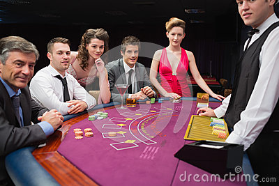 People sitting at the blackjack table smiling at the casino