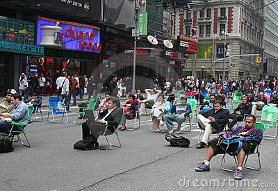 People sitting on folding chairs in Times Square Editorial Stock Image