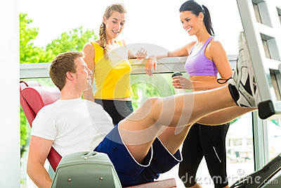 People in sport gym on the fitness machine