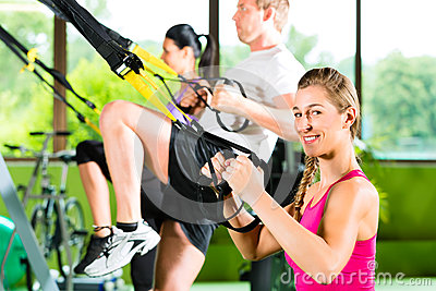 People in sport gym on suspension trainer