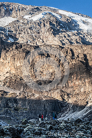 People standing before huge rock in mountain