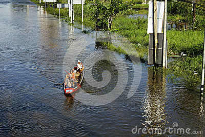 People travel by boat on the road during flood Editorial Stock Photo