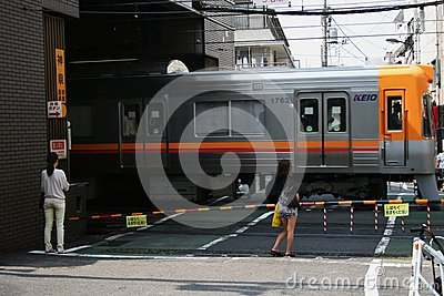 People wait as commuter train passes through street level crossing in central Tokyo. Editorial Image