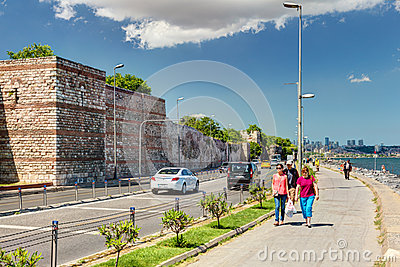 People walk along the promenade past the ancient sea walls of Co Editorial Photo
