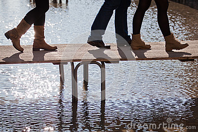 People walking at flood on a footbridge
