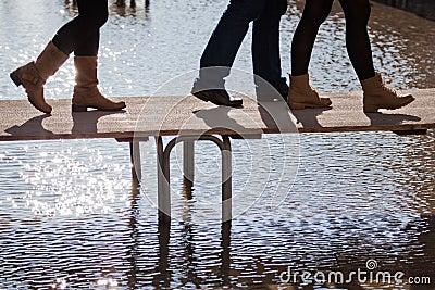People walking at flood on a footbridge