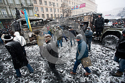 People walking inside the burned part of city with broked cars and buses in snow during winter anti-government protest Euromaidan Editorial Photography