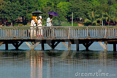 People walking over a wooden brigde