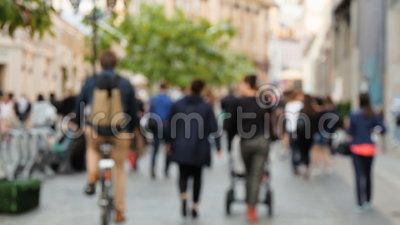 People walking on the street, not in focus. Slow motion