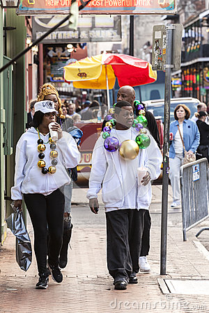 People wearing funny costumes celebrating famous Mardi Gras carnival on the street in French Quarter. Editorial Stock Photo