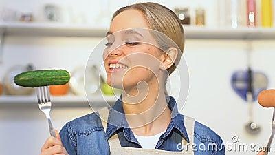 Pepino de mordedura da menina alegre, escolhendo entre o vegetal e a salsicha, vitaminas video estoque