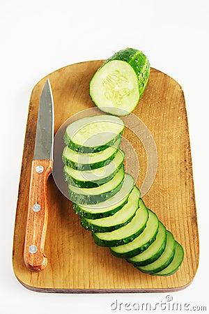 Pepino y cuchillo frescos maduros en la tabla de cortar