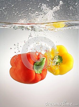 Peppers splashing in water