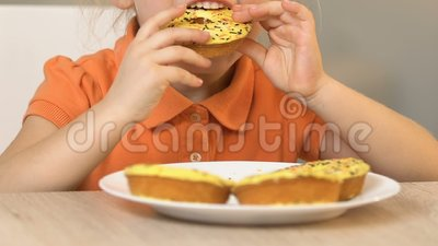 Pequeña muchacha codicioso que come los buñuelos sabrosos, comida preferida, alto nivel del azúcar almacen de video
