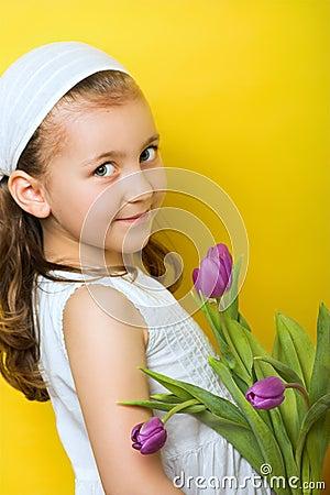 Pequeña muchacha sonriente con las flores
