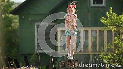Pequeño baile lindo de la muchacha en un tocón en la yarda de una casa de campo Feliz almacen de video
