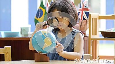 Pequeño estudiante asiático que mira el globo almacen de video