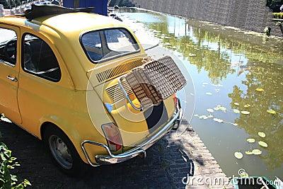 Pequeño coche italiano de la vendimia con la maleta de mimbre