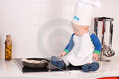 Pequeño cocinero del bebé en el sombrero del cocinero que hace las crepes