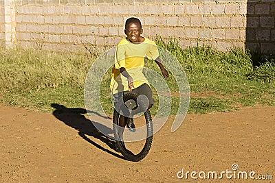 Pequeño muchacho que juega con el neumático