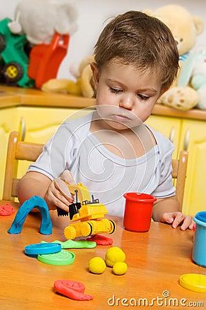 Pequeño niño que juega el plasticine