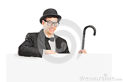 Performer in suit, retro hat and cane posing behing a panel