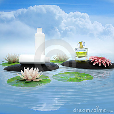 Perfume and flower on the black stones in water