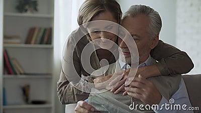 Periódico de la lectura del hombre mayor, mujer que viene de detrás abrazar, mañana de la familia almacen de video