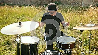Perkusista muzyczny ubrany w czarne ubrania, kapelusz, grający w zestaw bębnowy i cymbały zdjęcie wideo