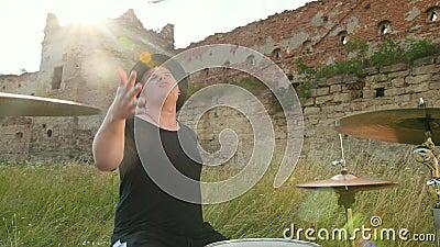 Perkusista muzyczny ubrany w czarny kapelusz, gra w zestaw bębnowy i cymbały, na ulicy zdjęcie wideo