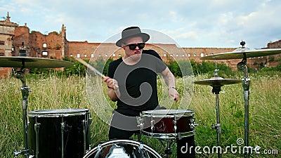 Perkusista muzyk ubrany w czarny kapelusz, grający w zestaw bębnowy i cymbały, na ulicy zbiory