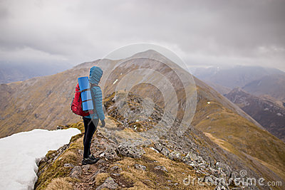 Person In Blue Hoodie Jacket Wearing Red Hiking Backpack Standing At The Top Of Mountain Under White Sky During Daytime Free Public Domain Cc0 Image