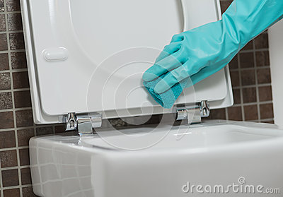 Hand of a person cleaning the toilet seat in rubber gloves with a